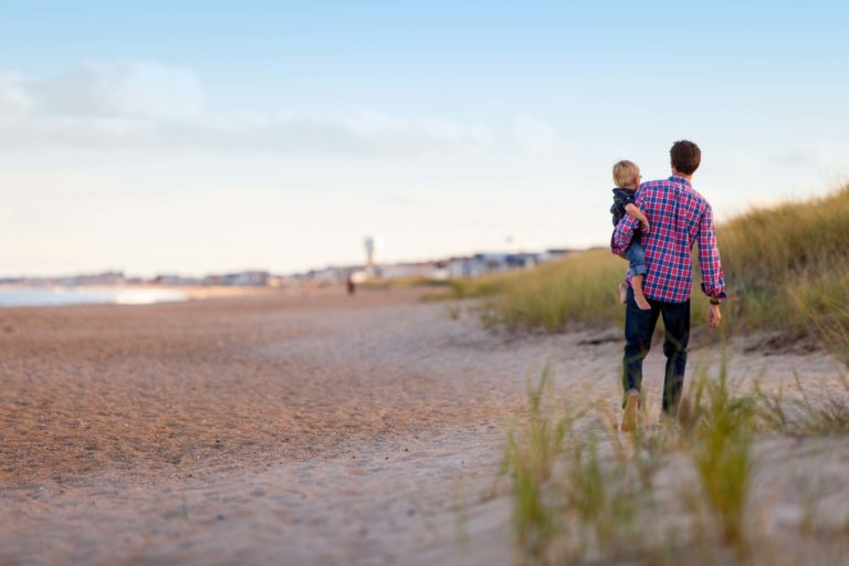 A father and his child walking on the beach.
