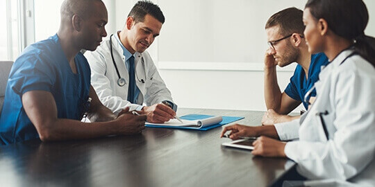 Physicians sitting at a conference table having a meeting