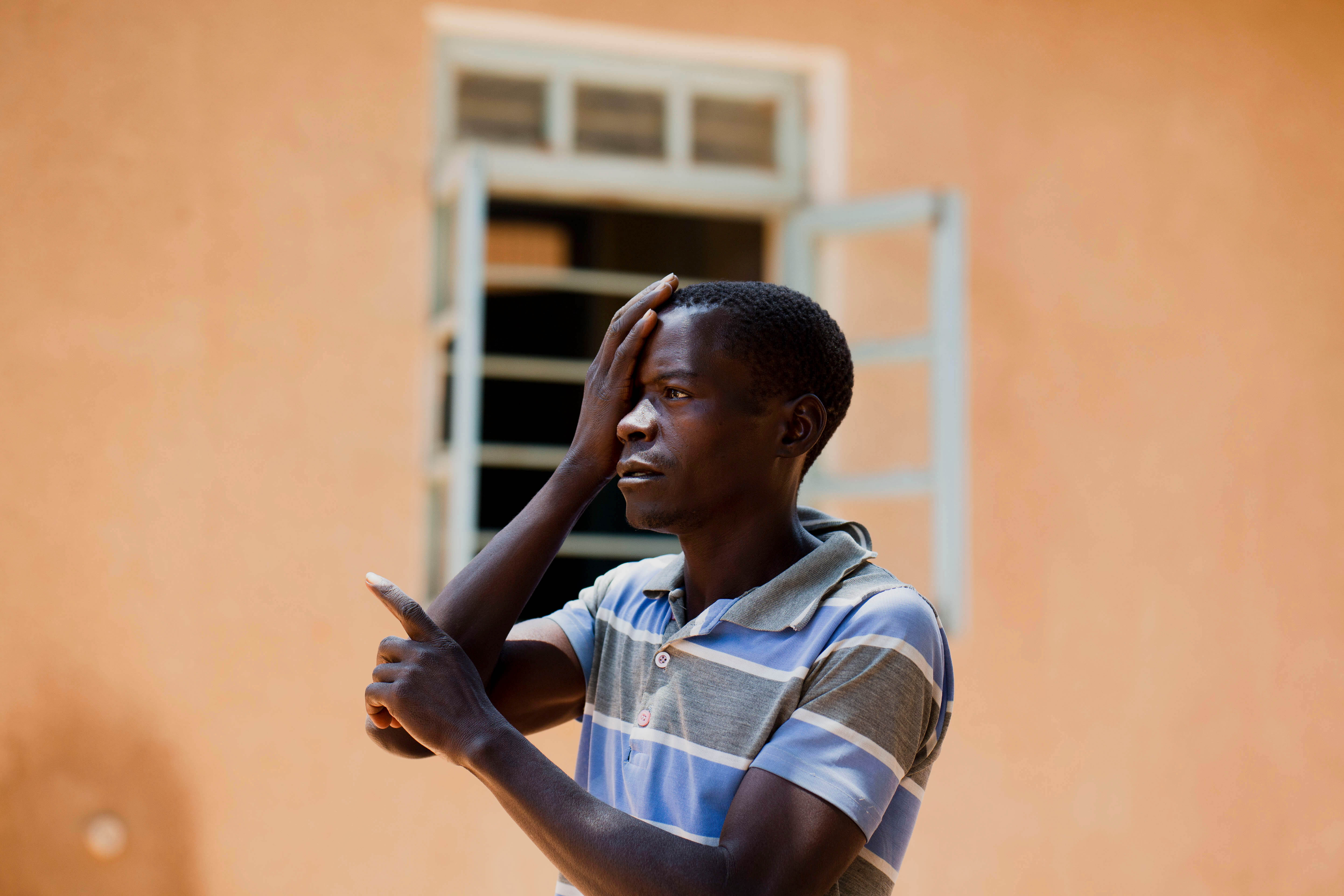 Tanzanian man pointing with eye covered.
