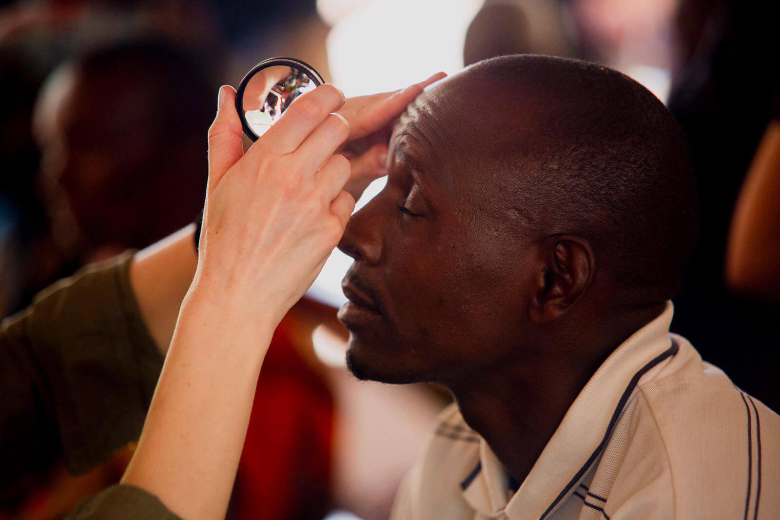 Tanzanian man getting his eyes examined.