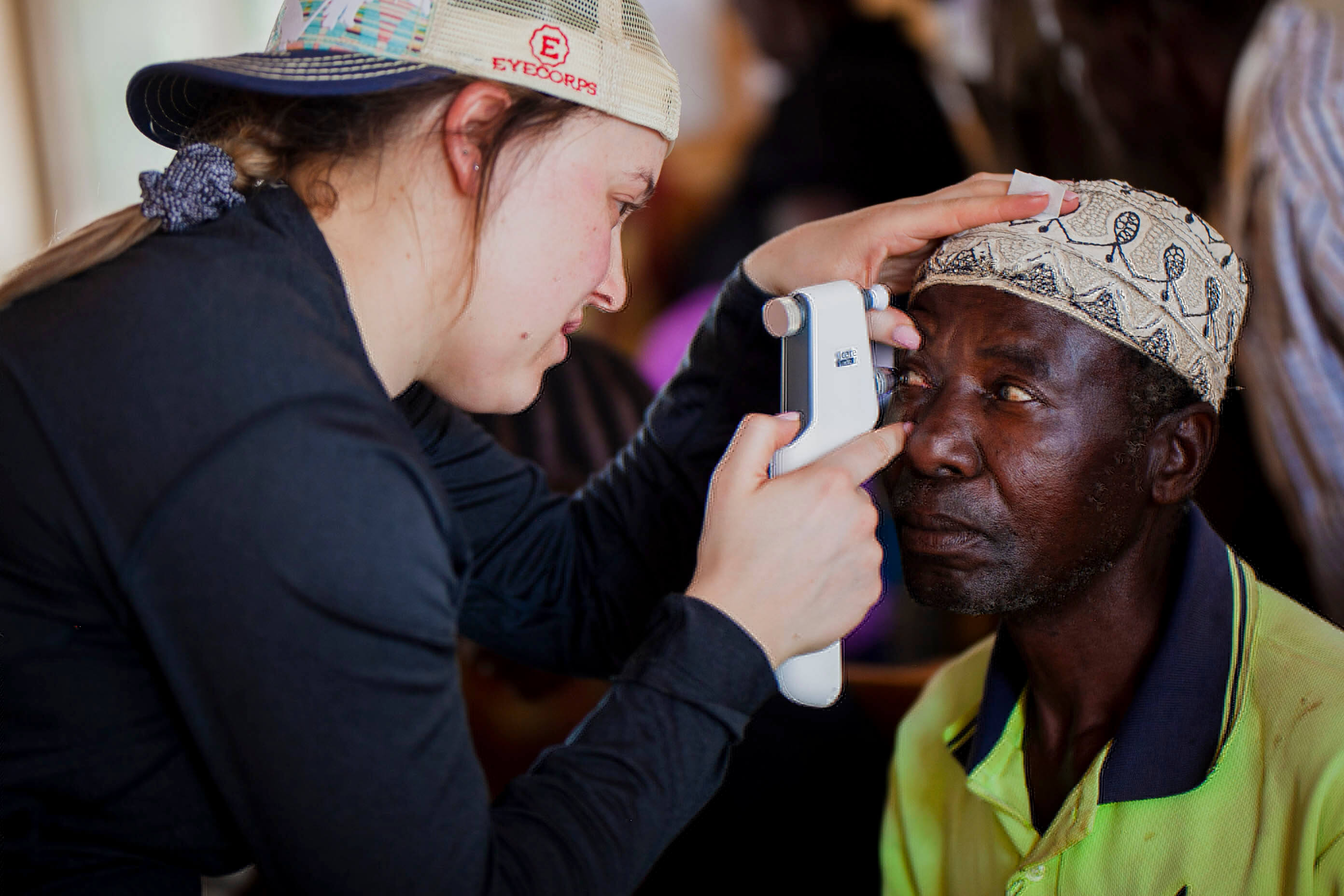 Medical staff examining eyes of Tanzanian man.
