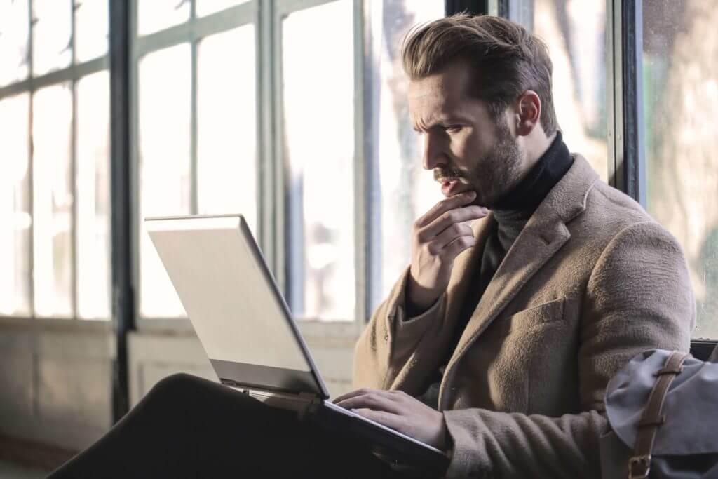 man wearing brown jacket and using grey laptop 874242 1024x683
