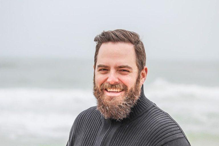 man wearing black zip up jacket near beach smiling at the 736716 768x512