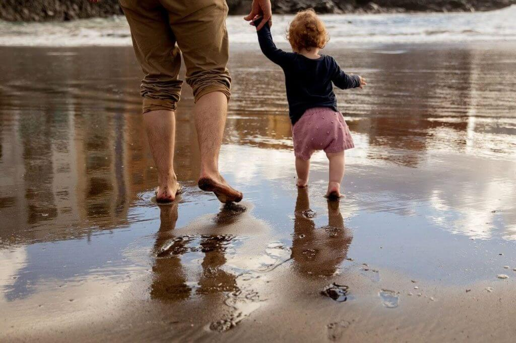 father and child walking on the shore 1024x682