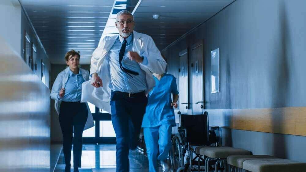 Physician running down hospital hallway