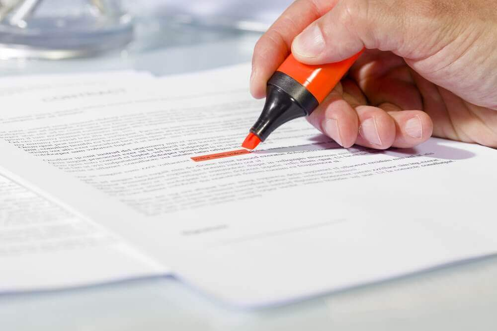 Person highlighting text on paper contract