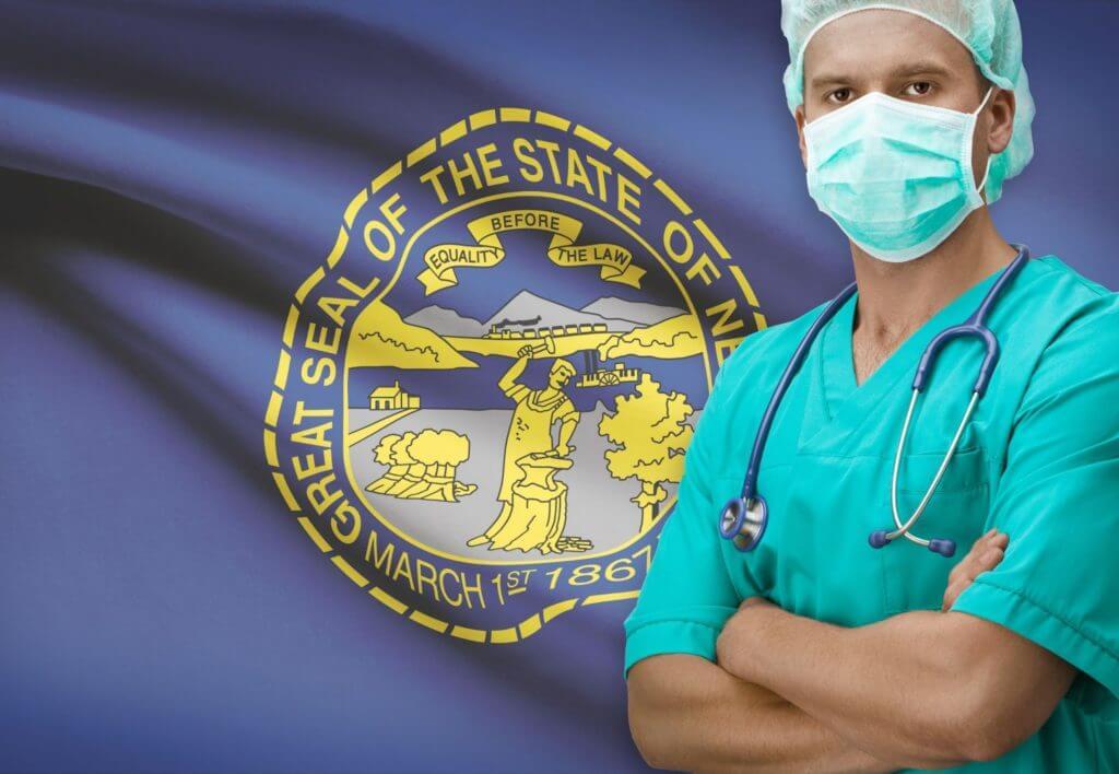 Physician standing in front of Nebraska state flag