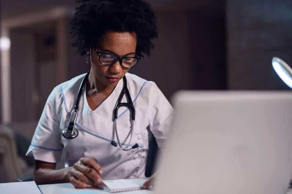 Physician sitting in front of computer looking at notepad